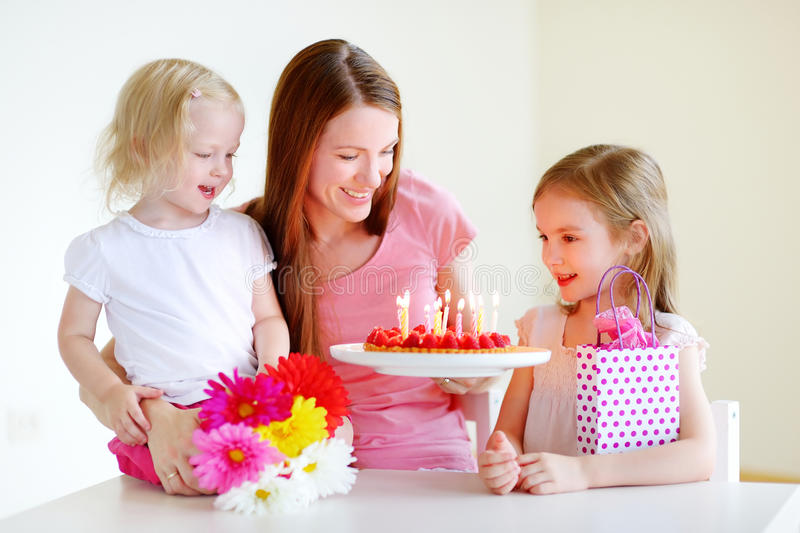 Mommy's birthday. Two little daughters kissing their mother wishing her a happy birthday stock images