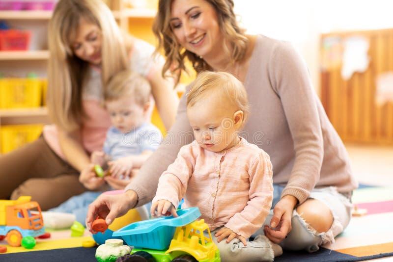 Moms με τα παιδιά που παίζουν στο πάτωμα Moms με το παιχνίδι κορών και γιων στο αυτοκίνητο στοκ εικόνες