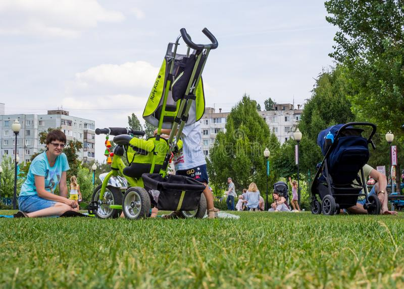 Moms with children rest on the lawn in the park `Arena`, the city of Voronezh stock image