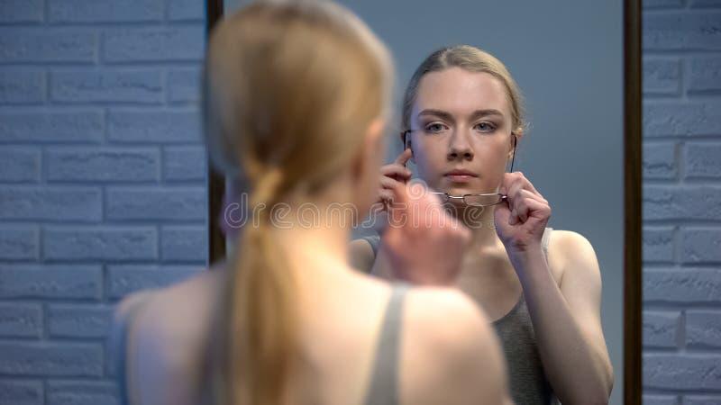 Monóculos de tentativa do adolescente atrativo que estão na frente da reflexão de espelho fotografia de stock royalty free