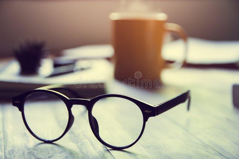 Monóculos e livros clássicos pretos, café quente do copo amarelo na tabela de madeira, dentro segunda-feira de manhã, primeiramen fotos de stock