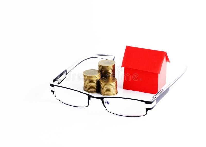 Monóculos e pilha das moedas do dinheiro e papel vermelho da casa para os empréstimos m imagem de stock