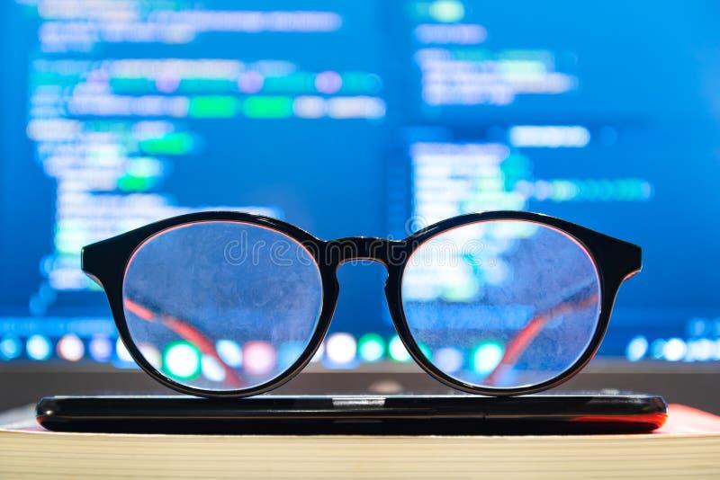 Monóculos na parte dianteira fora do tela de computador com sintaxe do código imagens de stock
