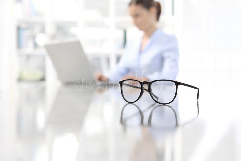 Monóculos que inclinam-se na mesa e na mulher que trabalham no computador no offi imagens de stock royalty free