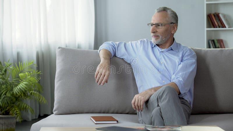 Monóculos vestindo saudáveis do homem superior, sentando-se no sofá, sonhando sobre o feriado imagem de stock