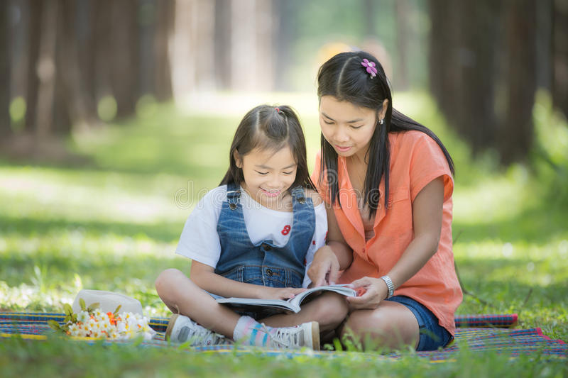 Mon and baby take a home work. On the green nature and flower garden stock image