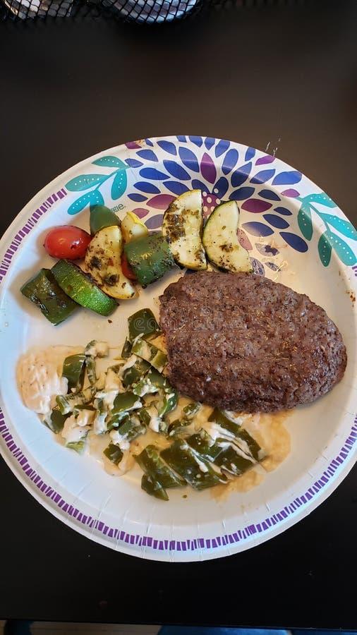 Mon hamburger de bison, chiches-kebabs de veggie et poivrons de jalapeno remplis de fromage fondu et de cheddar pointu photographie stock libre de droits