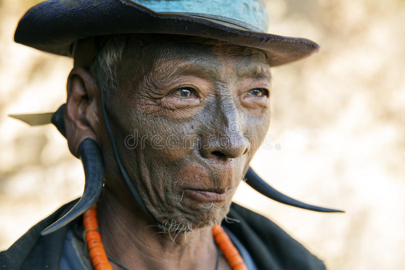 Mon Headhunter. Longwa, Nagaland/India - December 8, 2013: Elderly Tattooed faced former Mon Headhunter from Longwa Village. Naga tribes practised headhunting stock images