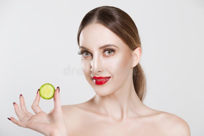 Mon masque est délicieux Une femme qui montre une tranche de concombre en regardant votre caméra souriant un arrière-plan blanc i photos libres de droits