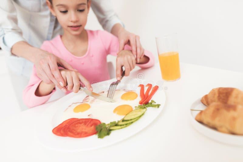 Mon petit déjeuner servi par mère pour sa fille Elle enseigne l'enfant à manger juste photos stock