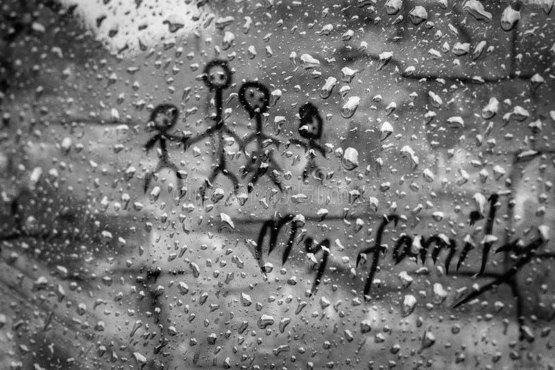 Mon texte de famille sur l'eau chute sur le vitrail en pleuvant la saison photo libre de droits