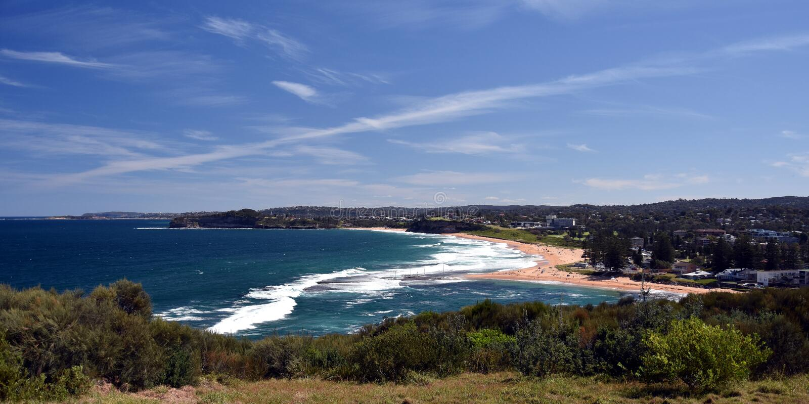 Mona Vale rock pool in a distant panoramic view from elevated lookout during high tide surfing waves and sandy beach, australia. Sydney northern beaches stock photography