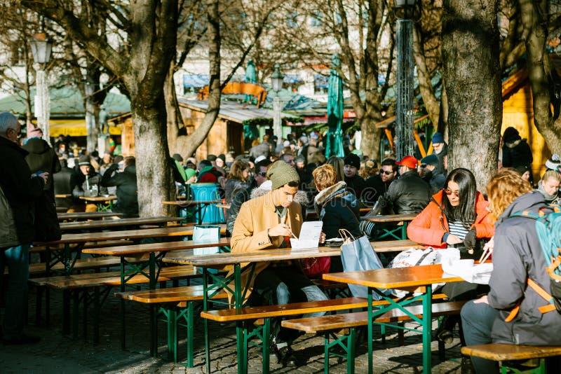 Monachium, Niemcy, Grudzień 29, 2016: Młody człowiek je w ulicznej kawie z fasta food i obywatela jedzeniem blisko centrali obraz royalty free