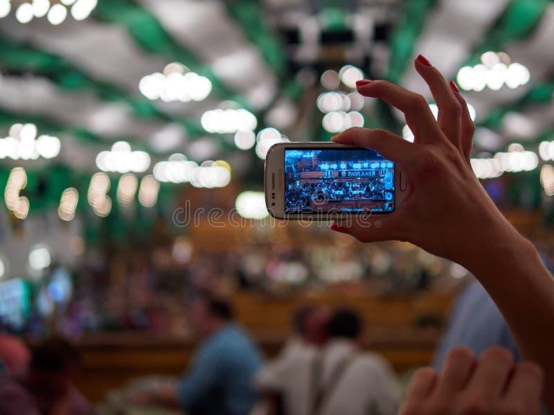 Monachium Niemcy, Wrzesień, - 21: Niezidentyfikowana dziewczyna robi fotografii namiot na Oktoberfest z jej telefonem komórkowym  obraz royalty free