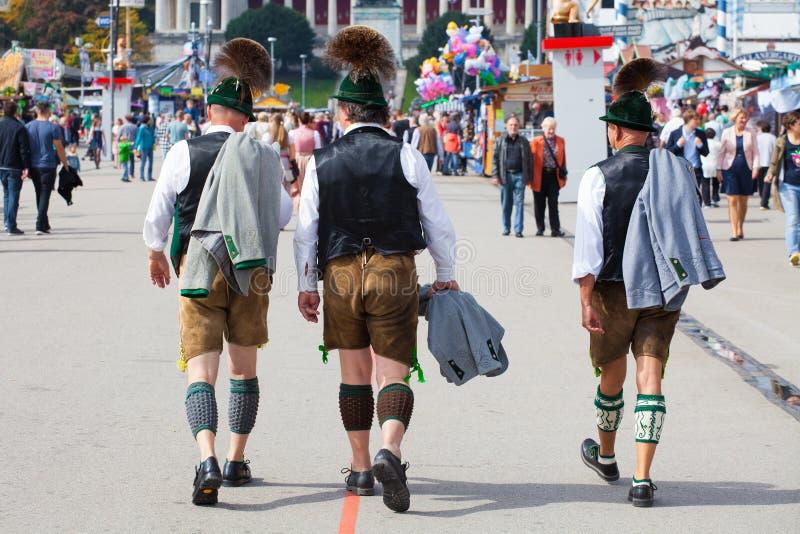 Monachium, wrzesień 27,2017: Trzy mężczyzna w tradycyjnego bavarian odzieżowych rzemiennych spodniach chodzą na Oktoberfest zdjęcie royalty free