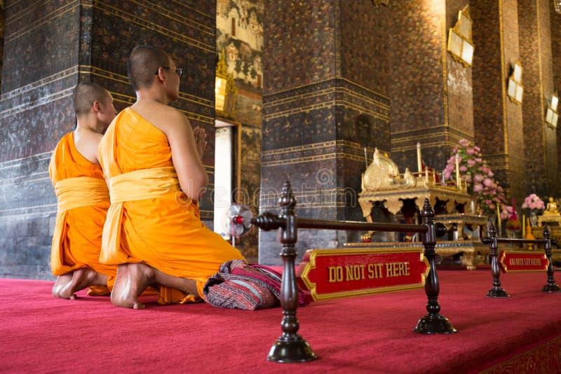 Monaci buddisti che pregano in tempio immagine stock