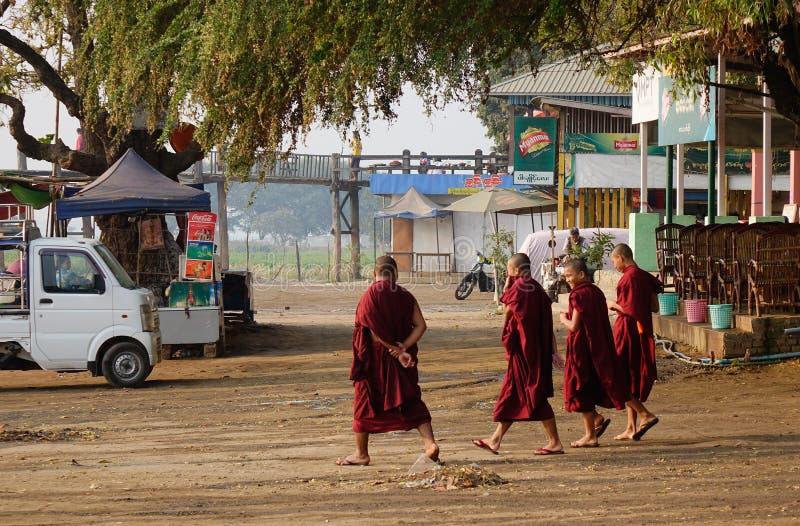 Monaci che camminano sulla strada della campagna a Mandalay, Myanmar immagini stock libere da diritti