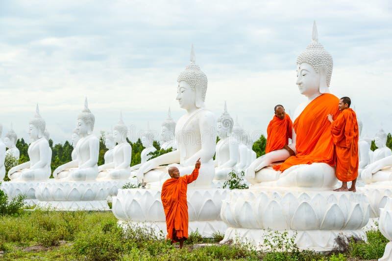 Monaci che vestono uno dell'immagine bianca di Buddha con gli abiti immagine stock