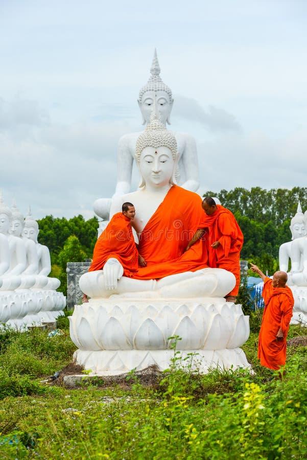 Monaci che vestono uno dell'immagine bianca di Buddha con gli abiti immagini stock