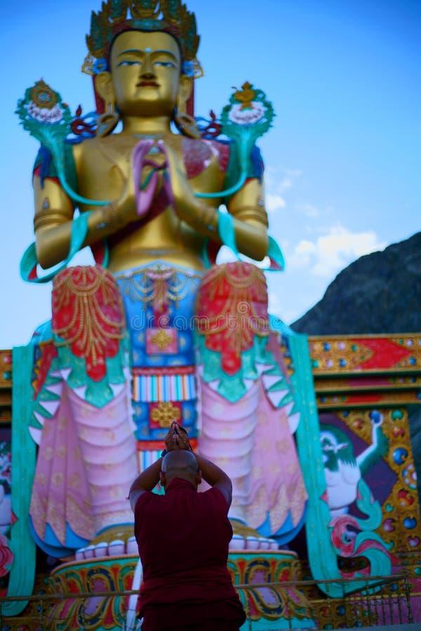 Monaco buddista che prega alla statua enorme di Buddha fotografia stock libera da diritti