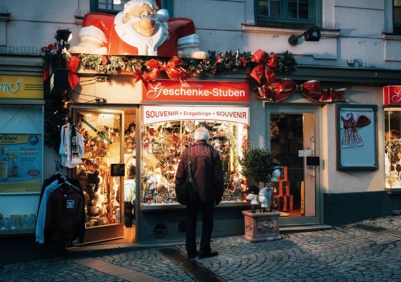 Monaco di Baviera, sguardi dell'uomo senior alla finestra del negozio sulla notte di Natale immagine stock