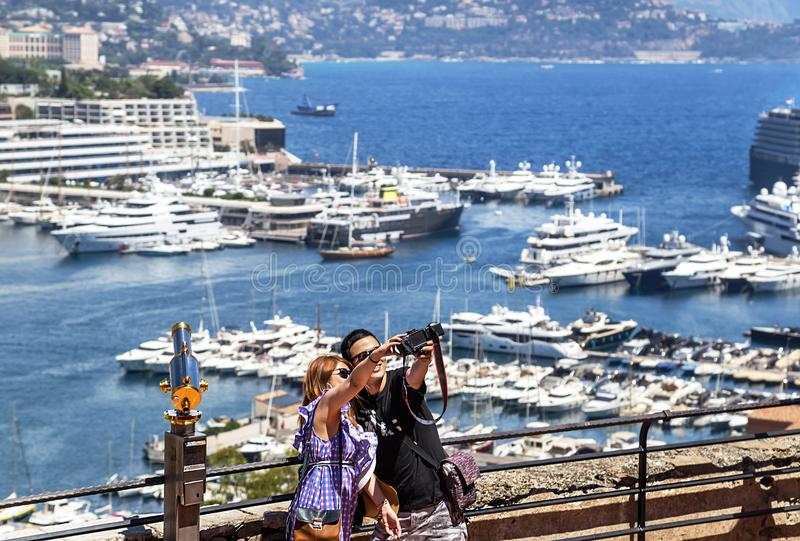Monaco, France – July 24, 2017: Young couple in love taking selfies in luxury Monaco (Monte Carlo). Sunny day, marina yachts background. France. Travel royalty free stock photo
