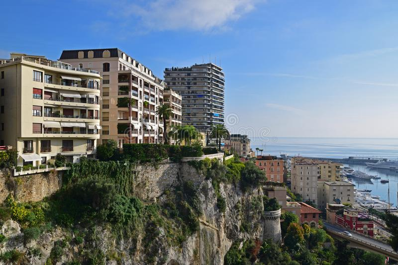 Residential buildings on top of dramatic cliff facing the harbour in the Principality of Monaco. Monaco is a sovereign city-state, country and microstate on the royalty free stock image