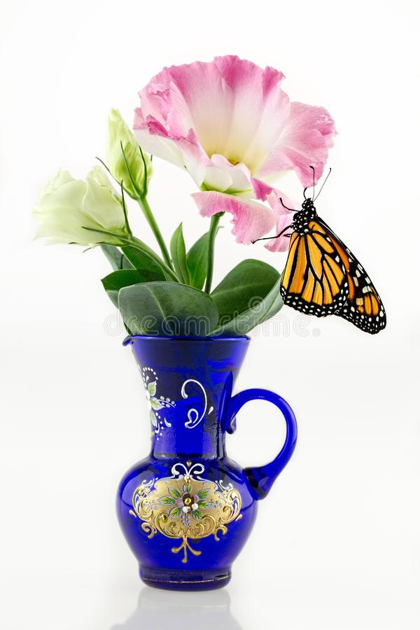 A Monarch Butterfly On A Flower In An Antique Vase stock images