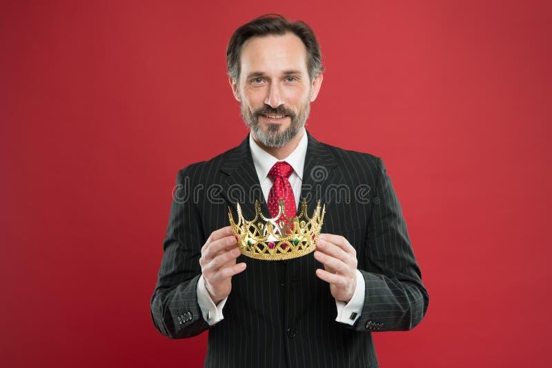 Monarchia atrybut Monarchii rodziny tradycje Obs?uguje brodatego faceta w kostiumu chwyta korony z?otym symbolu monarchia zosta? obrazy royalty free