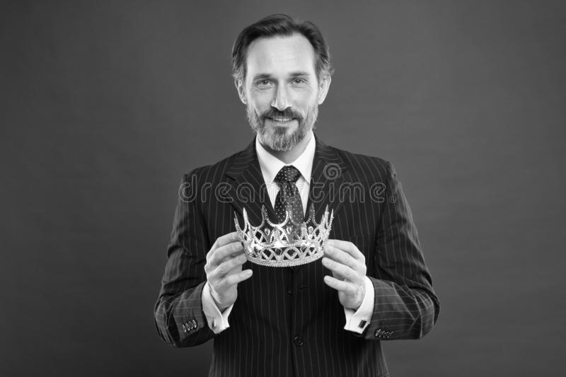 Monarchy attribute. Monarchy family traditions. Man bearded guy in suit hold golden crown symbol of monarchy. Become royalty free stock photo