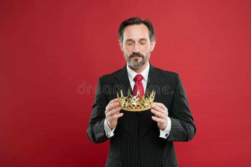 Monarchy family traditions. Man bearded guy in suit hold golden crown symbol of monarchy. Become king ceremony. Award royalty free stock photos