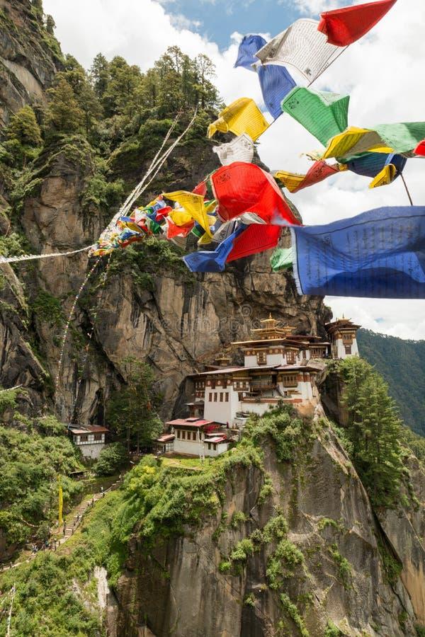 Monastère de Taktsang Palphug avec le drapeau de prière (également connu sous le nom de temple de nid de tigre), Paro, Bhutan photos stock
