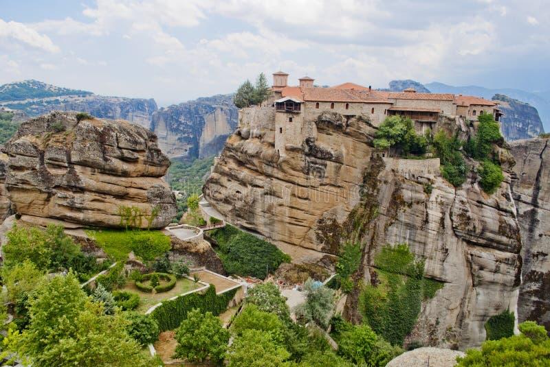 Monaster od Grecja z ampuły zieleni ogródem między wysokimi i brown skałami fotografia stock