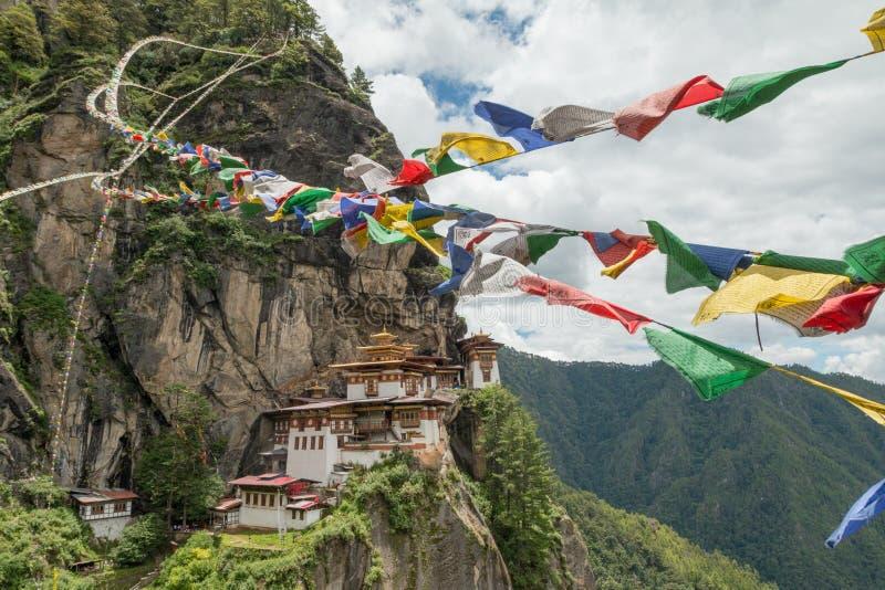 Monasterio de Taktsang Palphug con la bandera del rezo (también conocida como el templo de la jerarquía del tigre), Paro, Bhután imágenes de archivo libres de regalías