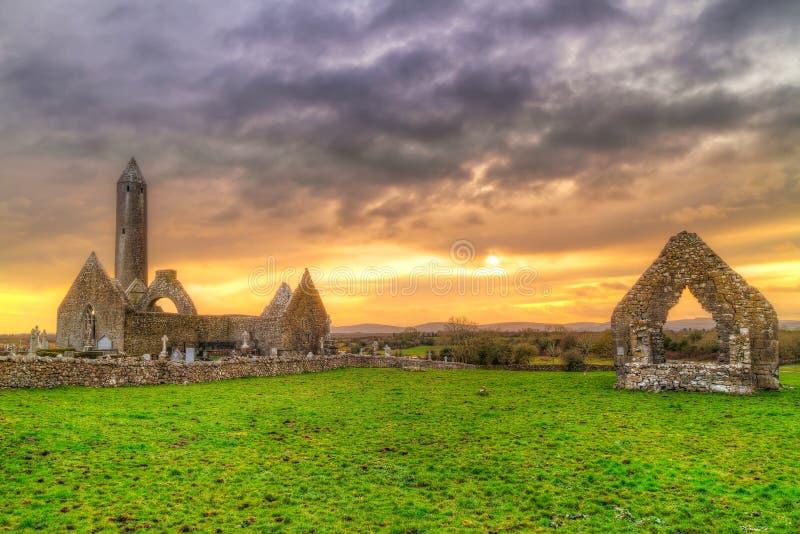 Monastero di Kilmacduagh con la torre di pietra al tramonto immagine stock libera da diritti