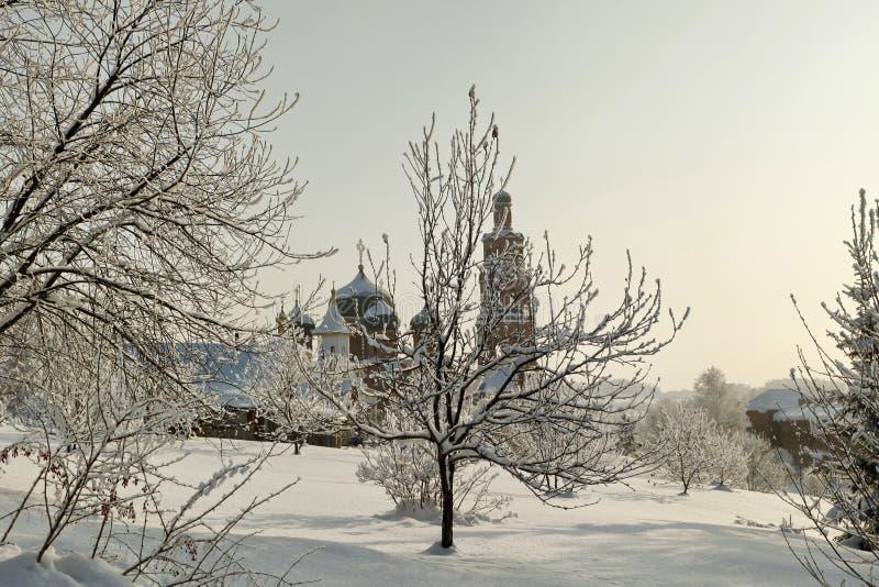 Monastero ortodosso dietro gli alberi nudi in neve profonda all'inverno immagini stock