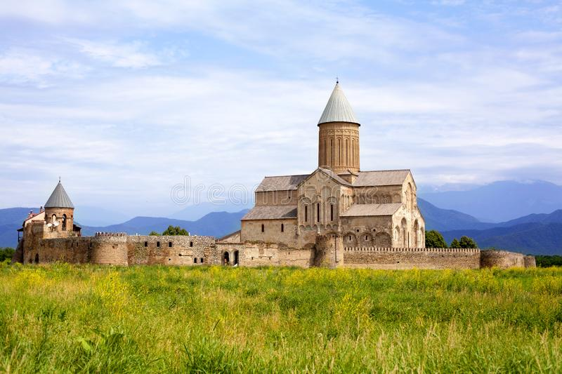 Monastery Alaverdi in Georgia, Kakheti region on a green field, mountains and blue sky with clouds background stock image