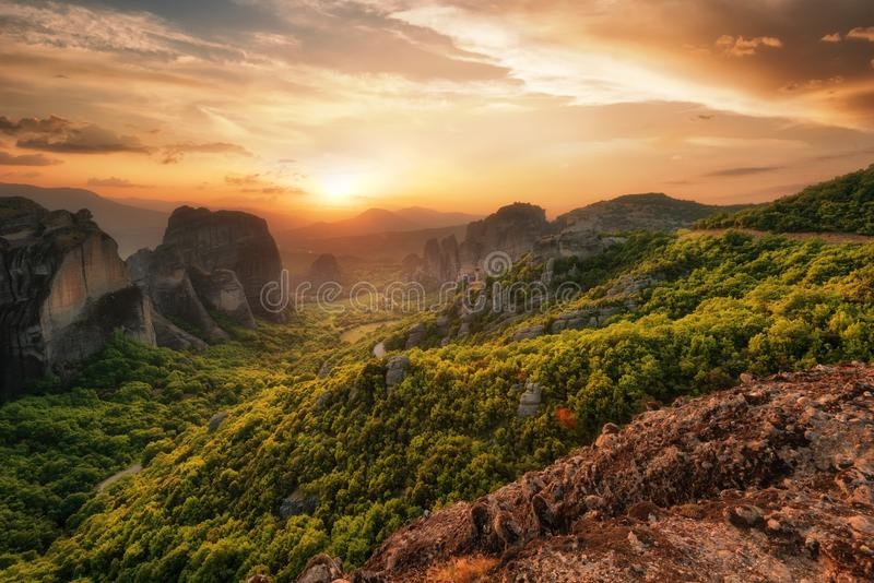 Monastery Meteora Greece. Stunning spring panoramic landscape at sunset. View at mountains and green forest against epic sky with clouds. UNESCO heritage list royalty free stock photo