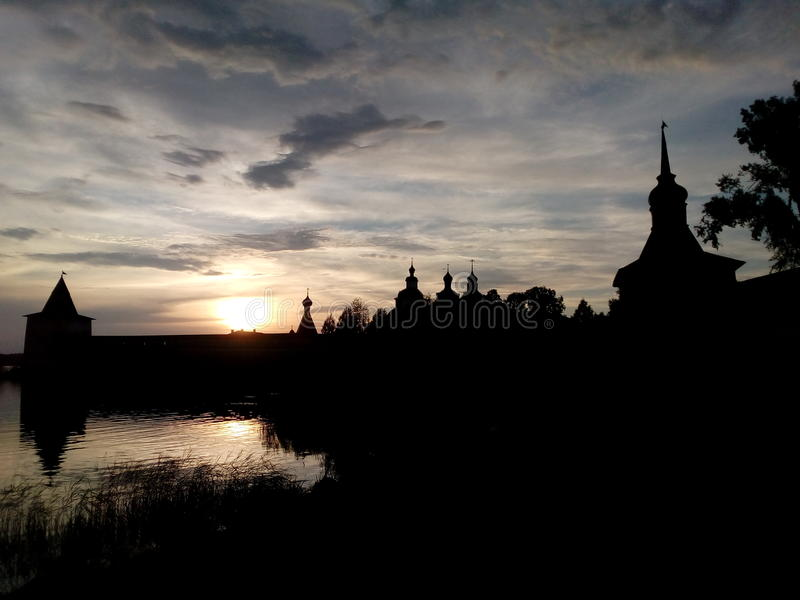 Monastery silhouette, lake, sky, sunset royalty free stock image