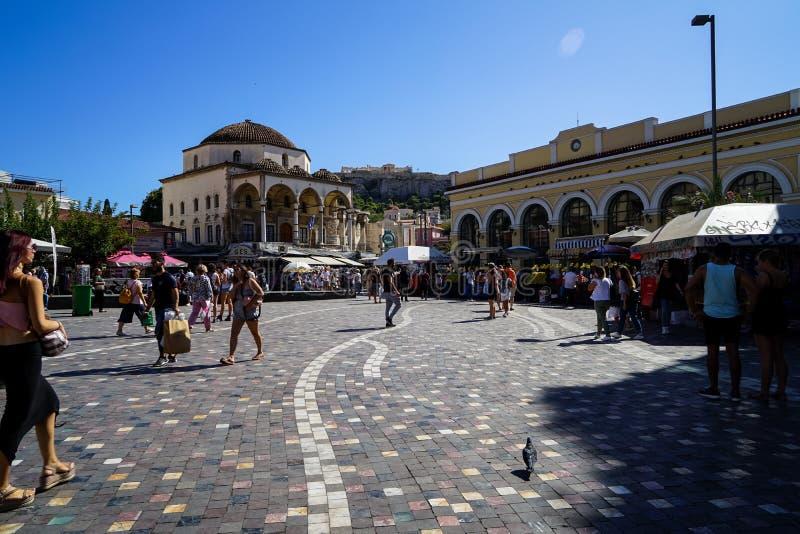 Monastiraki fyrkant på solskendag med den folkaktiviteter, marknaden, duvan och sikten av akropolen till och med gamla stadbyggna royaltyfria foton