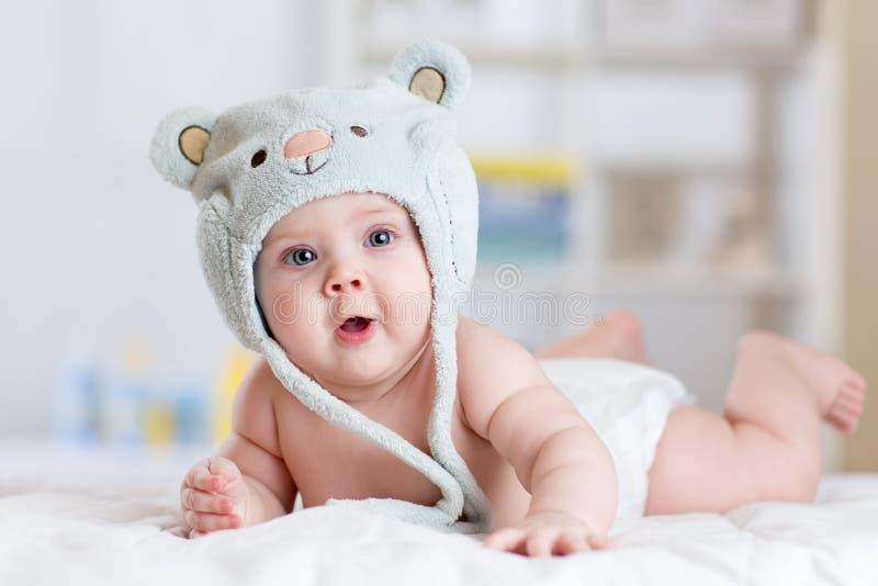 5 Monate Baby weared im lustigen Hut, der sich auf einer Decke hinlegt lizenzfreies stockbild