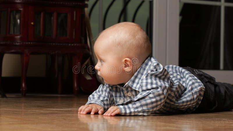 6 Monate männliches Kind, die auf Boden sitzen stockbild