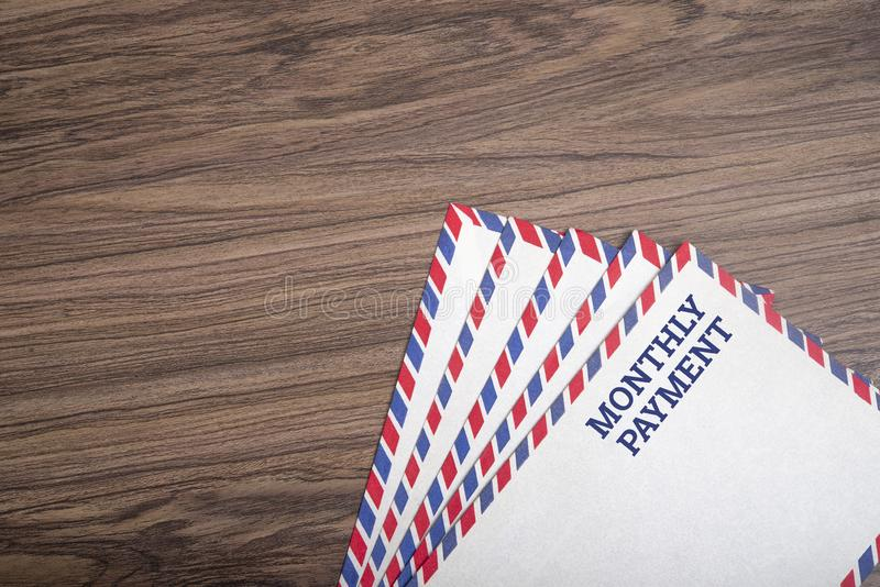 Monatliche Textzahlung auf Postkarte mit Holzhintergrund, Kopier-Leerzeichen stockfotos