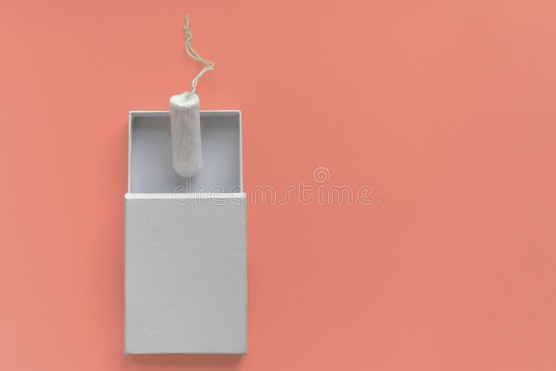 Monatszeitraumkonzept Frauenhygieneschutz Baumwolltampon in einem weißen boxon auf korallenrotem Hintergrund Kopienraum und -mode lizenzfreie stockfotografie