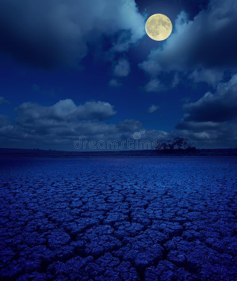 Mond in den Wolken über gebrochener Erde lizenzfreie stockfotos