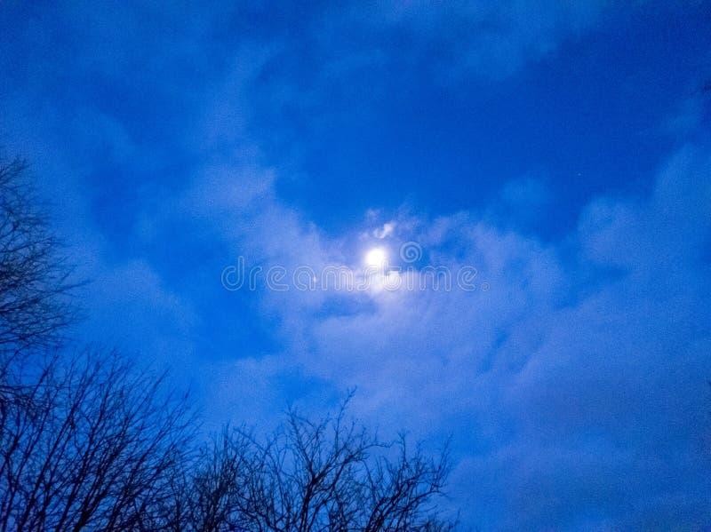 Mond an der Dämmerung gegen blauen Himmel stockfotos