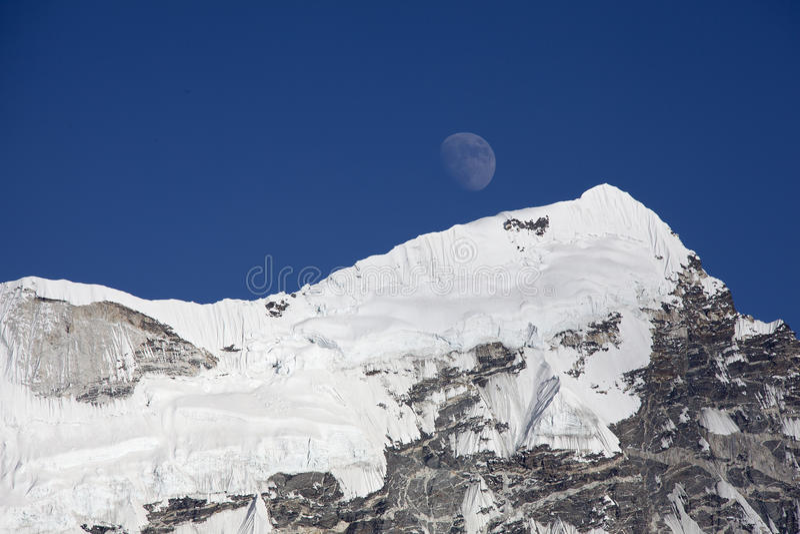 Mond und schneebedeckter Berg lizenzfreies stockfoto