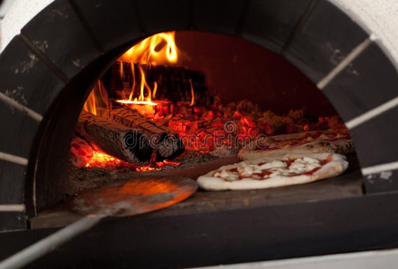 Mond-water gevende Italiaanse die pizza in een houten-brandt oven wordt gebakken stock afbeeldingen