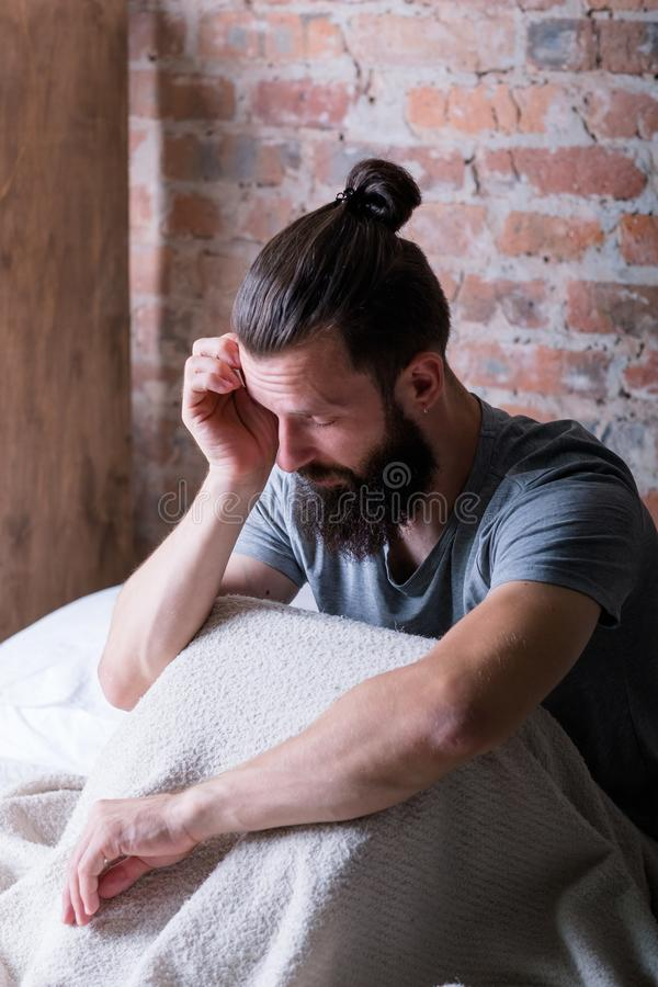 Monday morning drowsiness man bed tired sleepy. Monday morning again. Drowsiness. Man sitting in bed. Rubbing eye, looking tired and sleepy. Loft apartment stock images