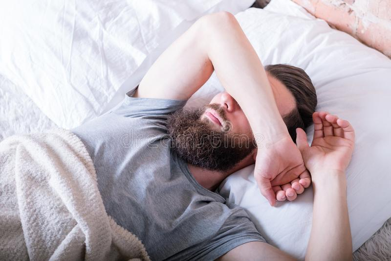 Monday morning laziness man bed covering eyes. Monday morning again. Laziness. Man lying in bed covering eyes with arm against daylight stock photos